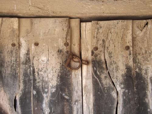 Portalada tradicional con puerta de madera y curioso cerrojo